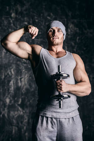 Muscular sportsman bodybuilder doing exercises with dumbbells. Health and sports concept.