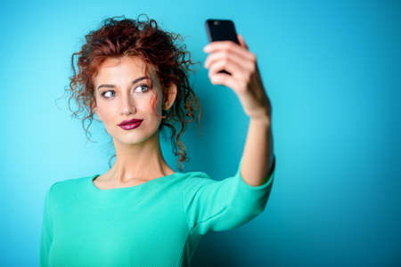 Beautiful red-haired girl in sunglasses over blue background making selfie on her cell phone. Beauty, fashion concept. Make-up and cosmetics. Studio shot.