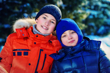 Two happy boys playing together outdoor on a sunny winter day. Snowfall. Winter clothes. Winter activity.