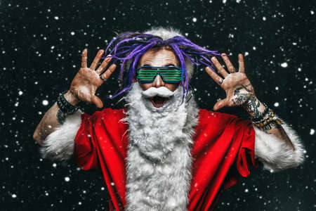 Portrait of a cool punk Santa Claus in luminous glasses with bright dreadlocks over black background.