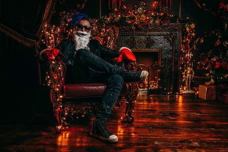 クリスマスに飾られた豪華なアパートメントで明るいドレッドロックを持つパンクサンタ。悪いサンタの概念。 写真素材