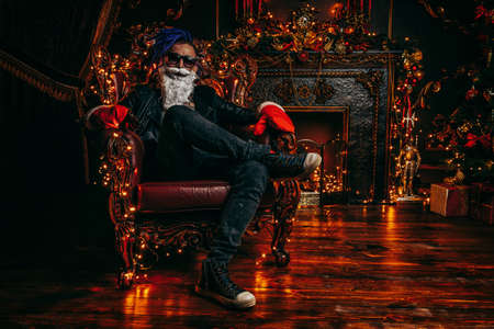 Punk Santa with bright dreadlocks  in luxurious apartments decorated for Christmas. Bad Santa concept.