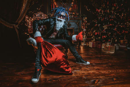 �¡heerful punk Santa with a bag of gifts in his hands  in luxurious apartments decorated for Christmas. Bad Santa concept.