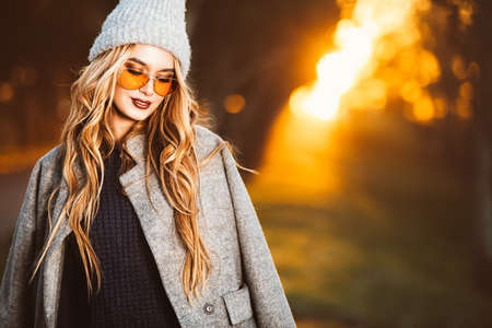 Autumn fashion. Happy young woman wearing warm sweater, a coat and a woolen hat walking in the park at a sunny autumn day. Standard-Bild