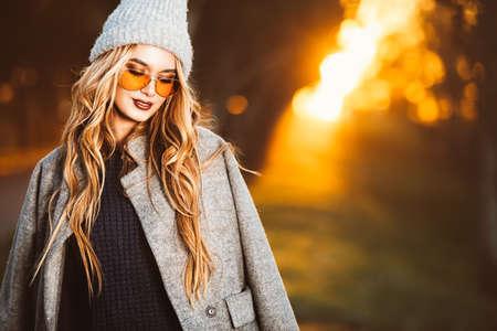 Herbstmode. Glückliche junge Frau, die die warme Strickjacke, einen Mantel und einen woolen Hut gehen in den Park an einem sonnigen Herbsttag trägt. Standard-Bild - 92295339