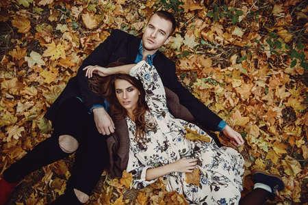 秋のファッション。黄色の秋の草や葉の上に横たわっている美しいファッショナブルなカップル。 写真素材