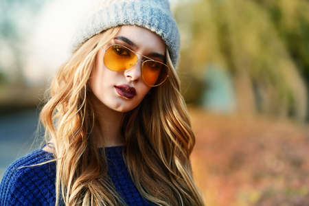Modern young woman wearing warm clothes posing in the autumn park. Autumn fashion. Stock Photo