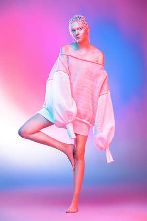 Fashion shot of a beautiful female model posing in designer clothes collection over pink background. Female beauty. Studio shot.