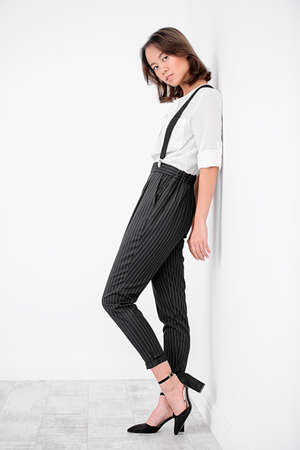 Young asian woman dressed in white shirt and classic trousers posing at studio. Business style in clothes. Fashion shot. 版權商用圖片 - 92295818