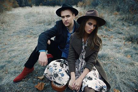 秋のファッション。黄色の秋の草や葉に美しいファッショナブルなカップル。