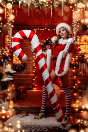 Sexy Santa girl in red body suit and striped stockings holds a big lollipop and poses near the house of Santa, decorated with festive lights. Christmas and New Year concept. Stock Photo