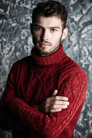 Portrait of a handsome young man in a warm sweater. Autumn, winter clothes. Male beauty, fashion. Banque d'images