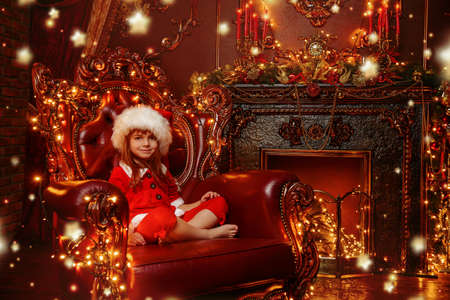 Pretty five-year-old girl in the suit of Santas helper sits in an armchair in a beautiful room. Luxurious apartments decorated for Christmas.  Stock Photo