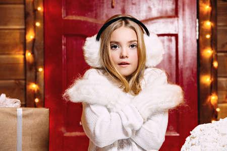 예쁜 아이 소녀 모피 귀고리와 장갑에 크리스마스 장식 그녀의 집 근처에 서있다. 따뜻한 겨울 액세서리. 즐거운 성탄절 보내시고 새해 복 많이 받으세 스톡 콘텐츠