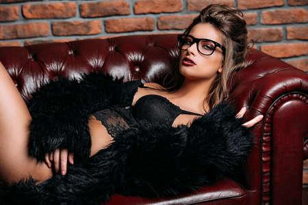 革張りのソファに横たわる黒いランジェリーと毛皮のジャケットを着た魅惑的な女の子。贅沢なライフスタイル。ファッション、美しさスタジオシ