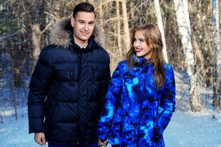 Paare der jungen Leute in der Winterkleidung im Park . Winter Mode . Daunenjacke