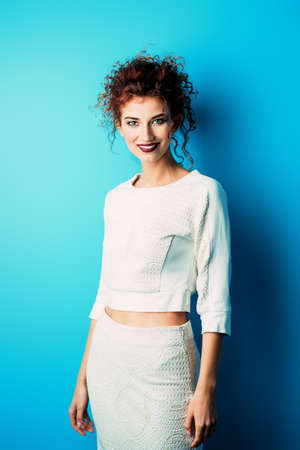 Portrait of the attractive young woman with bright red curly hair and make-up over blue background. Beauty, fashion. Business style in clothes. Studio shot. Stock Photo