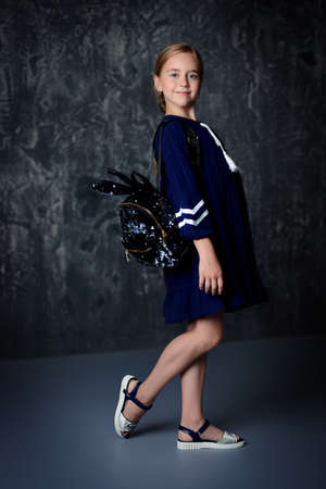 Portrait of a cute ten-year-old girl smiling at camera. Children's fashion. Full length portrait.