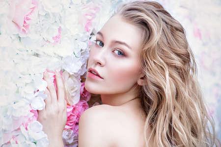 Mujer joven romántica hermosa con el maquillaje natural que presenta en un fondo de rosas. Perfume, concepto de cosmética. Foto de archivo