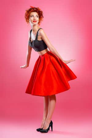 아름 다운 감정적 인 젊은 여자 핑크 배경 위에 스커트와 위쪽 블라우스 포즈를 입고. 핀업 스타일. 패션 스튜디오 촬영. 전체 길이 초상화. 스톡 콘텐츠