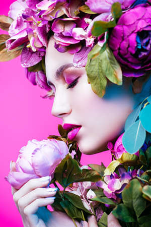 Sensual spring lady in a wreath of flowers over pink background. Inspiration of spring and summer. Perfume, cosmetics concept.