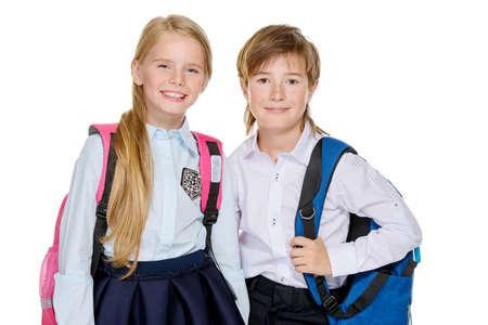 La mode scolaire. Deux enfants mignons en uniforme et avec des sacs à dos se présentant au studio. Isolé sur fond blanc Espace de copie. Banque d'images - 93628532