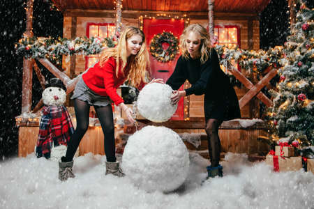 Happy girls in beautiful winter clothes make a snowman near the house, decorated for Christmas. Time of miracles. Merry Christmas and a Happy New Year. Banco de Imagens