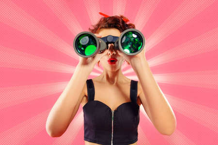 Pretty red-haired girl looks through binoculars at something over pink background. Pin-up style.