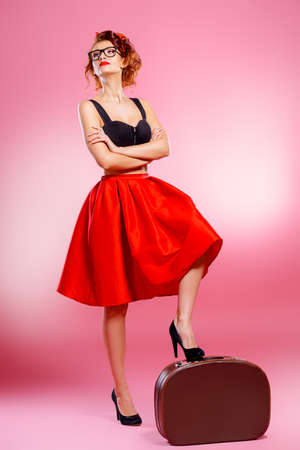 Pretty pin-up girl with suitcase poses over pink background. Tourist trip concept. Copy space.