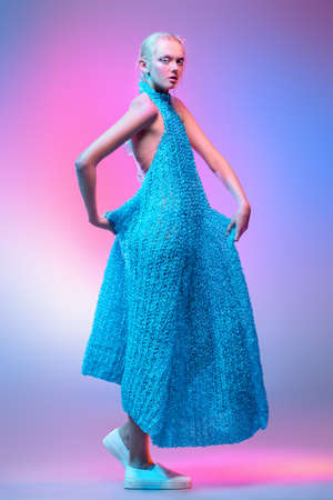 Vogue shot of a female model posing at studio in a long knitted dress. Fashion collection. Full length portrait over pink background.