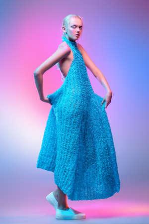 Vogue tir d & # 39 ; un modèle féminin posant au studio dans une longue robe tricotée . collection pleine longueur portrait sur fond rose . Banque d'images - 93628633