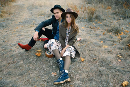 Autumn fashion. Beautiful fashionable couple on yellowed autumn grass and leaves.