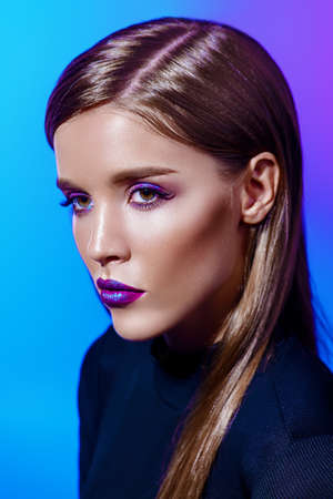Portrait of an attractive girl with bright makeup and violet lips. Styling for long hair. Modern youth fashion. Stock Photo