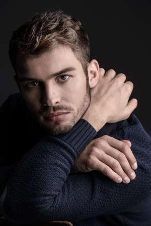 スカーフとセーターのハンサムな若者。スタジオの肖像画。秋と冬の服。男性のファッション。