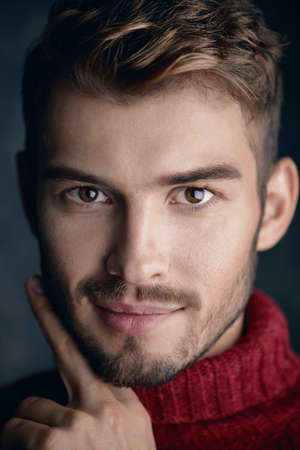 Portrait of a handsome smiling young man in a warm sweater. Autumn, winter clothes. Male beauty, fashion.