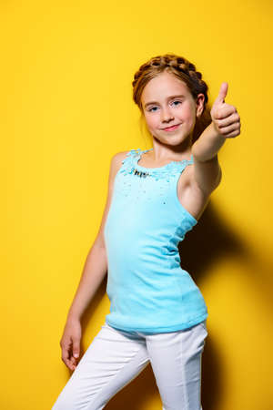 Bright summer girl. Cute cheerful eight-year-old girl in summer clothes posing over yellow background. Foto de archivo