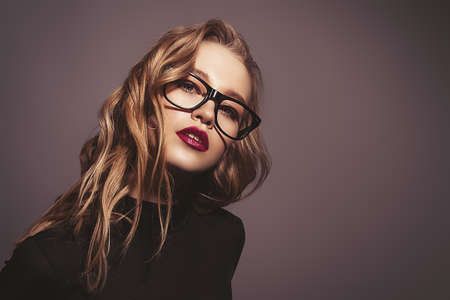 Attractive young woman in spectacles. Studio shot. Beauty, fashion concept. Optics style. Stock Photo
