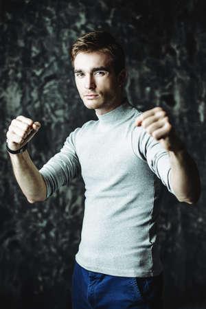 Ritratto di un giovane serio pronto a colpire. La forza e la salute dell'uomo. Archivio Fotografico - 94499264