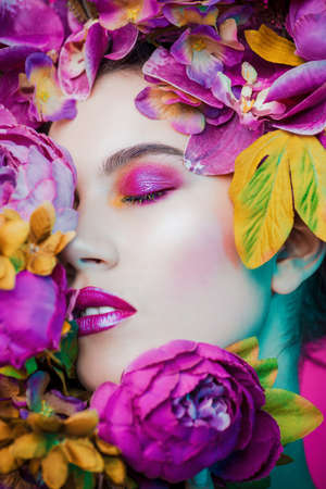 Beauty portrait. Beautiful brunette woman with sensual lilac lips surrounded by flowers. Spring look. Cosmetics, make-up. Perfumery. Stock fotó