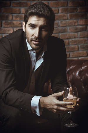 Portrait of a sexy handsome man drinking wine on a leather sofa. Luxurious lifestyle. Fashion shot. Men's clothing and accessories.