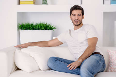 Handsome man wearing white t-shirt and jeans is resting at home on the couch. Mens beauty and health.