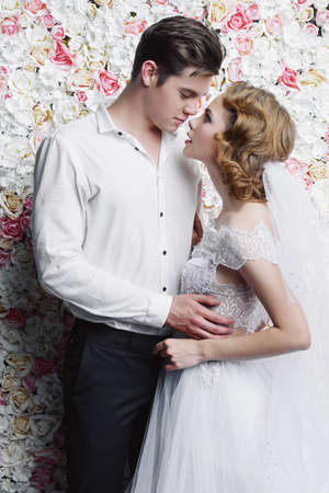 Loving bride and groom stand in tender embrace. Wedding fashion. Stock Photo