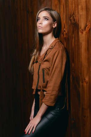 茶色のジャケットと木製の壁でポーズをとる革のズボンを着たかわいい若い女性。若者のスタイル、ファッション。