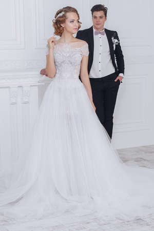 Beautiful loving bride and groom stand in luxurious apartments. Wedding fashion.