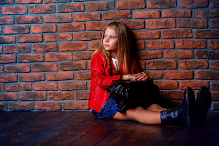 Modern eight year old girl posing by the brick wall. Urban style clothes. Children's fashion.
