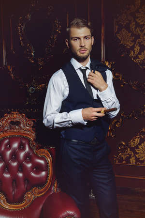 고전적인 인테리어가있는 호화로운 아파트에서 잘 차려 입은 남성을 부과합니다. 사치. 남자의 아름다움, 패션.