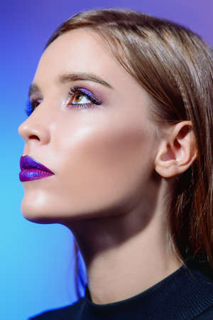 Close-up portrait of an attractive girl with bright makeup and violet lips. Beauty, fashion. Cosmetics, make-up.