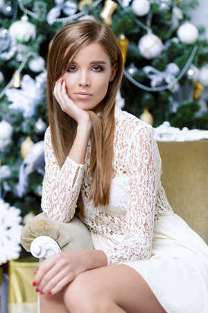 Beautiful young woman in white evening dress posing near the Christmas tree in luxurious apartments. Beauty, fashion. Christmas, winter holidays concept.