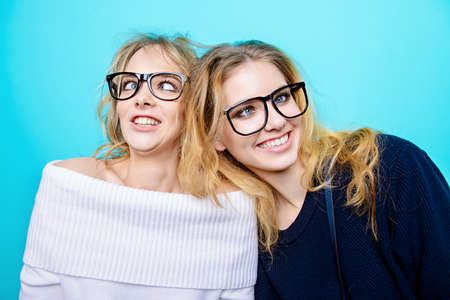 two pretty cheerful girls in glasses make faces in studio over