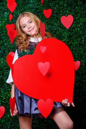Happy pre-teen girl holding red heart entouré de petits coeurs sur fond de pelouse. Premier amour. La Saint-Valentin.